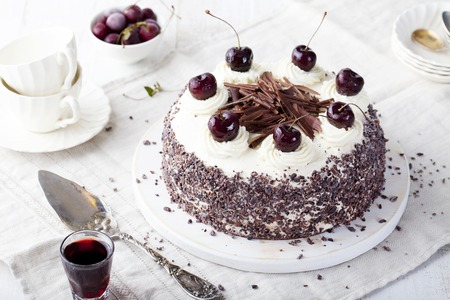 to black: Black forest cake, Schwarzwald pie, dark chocolate and cherry dessert on a white wooden background Stock Photo