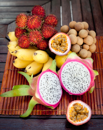 fruta tropical: Assortment of tropical exotic fruits: dragon fruit, bananas, passion fruit, longan, rambutan on a wooden background