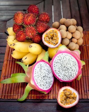 fruta tropical: Surtido de frutas tropicales exóticas: fruta del dragón, plátanos, fruta de la pasión, longan, rambután en un fondo de madera Foto de archivo