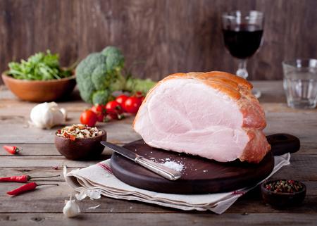Varkensvlees ham op een houten snijplank met verse salade en groenten. Stockfoto