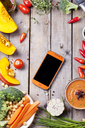cope: Fresh vegetables with mobile cell phone on a wooden background. Cope text space.