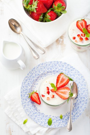 Strawberry tiramisu, trifle, custard dessert in a glass with fresh strawberry and mint leaves on a white wooden background