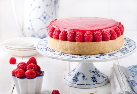 Raspberry and roast bell pepper mousse cake, cheesecake with fresh chili pepper on a white wooden background Stock Photo