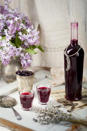 ブラックカラント ライラック色の花と木の背景で自家製の酒