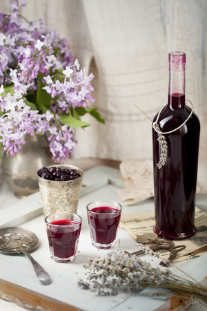 Blackcurrant homemade liquor on a wooden background with lilac flowers Reklamní fotografie - 47722622