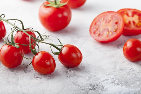 ensalada tomate: Tomates frescos con la sal del mar con un tomate reducido a la mitad en el primer plano. Fondo de piedra