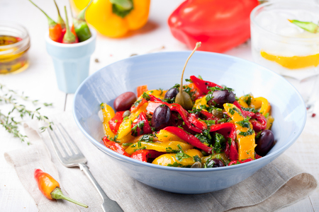 grilled vegetables: Roasted yellow and red bell pepper salad with capers and olives in a blue bowl on a white background. Grilled vegetables.