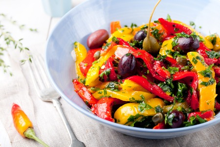 spanish food: Roasted yellow and red bell pepper salad with capers and olives in a blue bowl on a white background. Grilled vegetables.