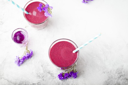 acai berry: Blueberry, blackberry, honeysuckle, honeyberry smoothie with violet syrup and acai berry powder on a stone background. Stock Photo
