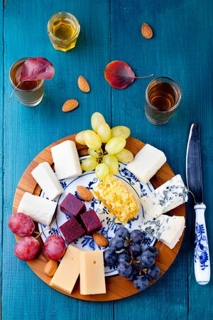 dairy product: Cheese plate with fresh grape, honey comb, nuts and plum jelly, marmalade on a blue wooden background