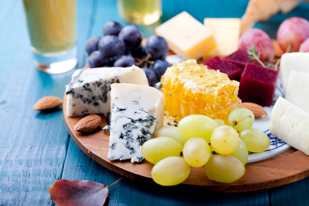 honey comb: Cheese plate with fresh grape, honey comb, nuts and plum jelly, marmalade on a blue wooden background