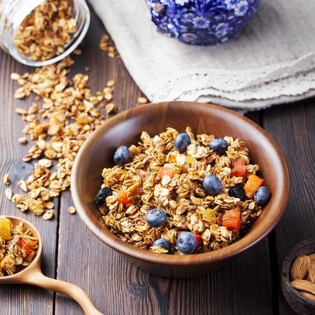 breakfast: Desayuno saludable. Granola fresca, muesli con frutas, miel y leche en un cuenco de madera sobre un fondo de madera