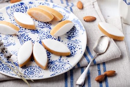 흰색 나무 배경에 세라믹 접시에 Calissons 디부 엑상 프로방스. 전통적인 프랑스 프로방스 과자입니다.