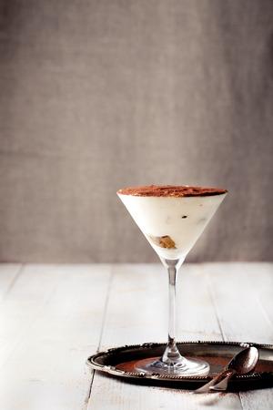 Tiramisudessert in een glas op een witte houten achtergrond, traditionele Italiaanse. Stockfoto
