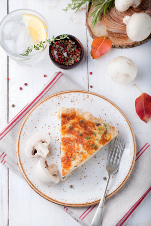 baked chicken: Mushroom, champignon pie, quiche slice on a ceramic plate on a white wooden background Stock Photo