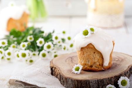 Kleine Pasen-cake, kulich, dwarsbroodje op een witte de lenteachtergrond. Traditionele Russische Pasen-cake.