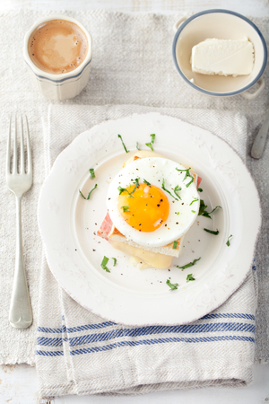 eggs: Croque madame, egg, ham, cheese sandwich with a cup of coffee. Traditional French cuisine. Breakfast table.