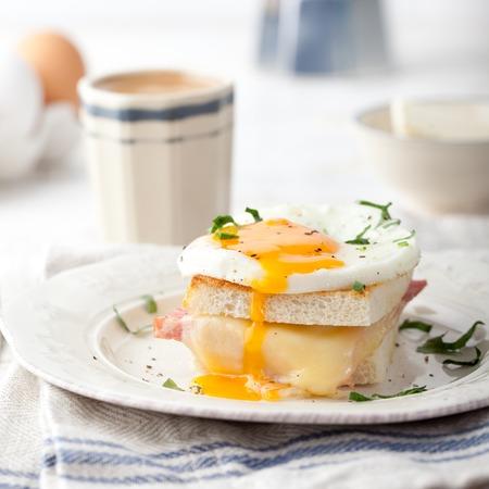 Señora de Croque, huevo, jamón, queso con una taza de café. Cocina francesa tradicional. Mesa de desayuno.