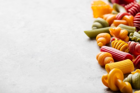 variety: Different colorful handmade pasta variety on a grey stone background.