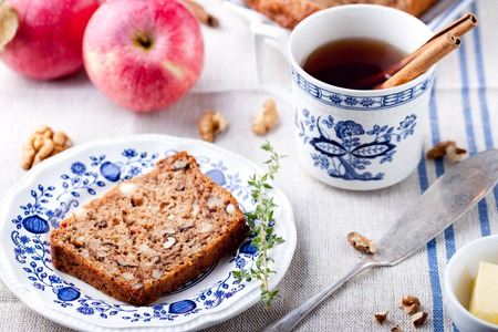 walnut cake: Apple, walnut cake, loaf, bread with fresh apples and cinnamon sticks on a textile blue and white background.