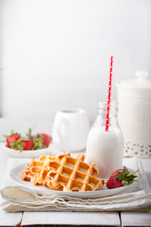 Fresh waffles with a bottle of milk om a white background.