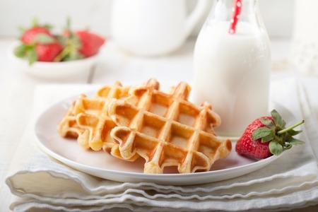 colazione: cialde fresche con una bottiglia di latte om uno sfondo bianco.