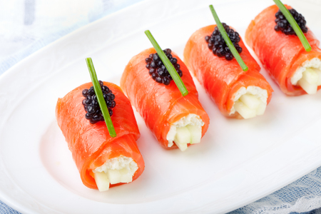 Smoked salmon rolls with cream cheese, cucumber, black caviar and chives