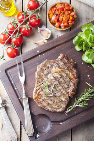 Beef steak well done with tomato and pepper salsa on a dark wooden background