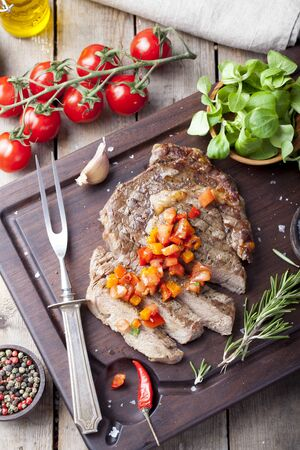 done: Beef steak well done with tomato and pepper salsa on a dark wooden background