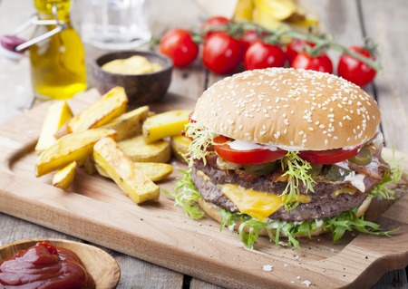 Burger, hamburger with frech fries, ketchup, mustard and fresh vegetables on a dark wooden background