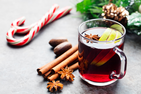 Mulled red wine with apple slices and spices in a glass cup on a Christmas background Stock Photo