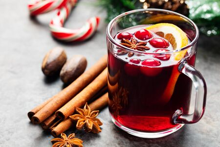 spiced: Mulled red wine with spices, cranberries, orange slices on grey stone new year and christmas background