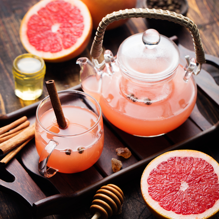 toronja: Pomelo t� de hierbas con especias y miel en un vaso de agua y taza de cristal sobre un fondo de madera oscura