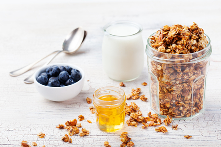 yogur: Desayuno saludable. granola fresca, muesli en un frasco de vidrio con el yogur, arándanos frescos y miel en un fondo de madera blanca