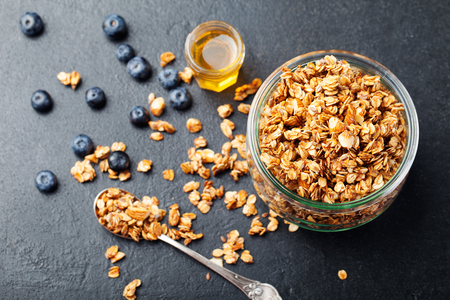 Healthy breakfast. Fresh granola, muesli with berries, honey in a glass jar on a black slate background.