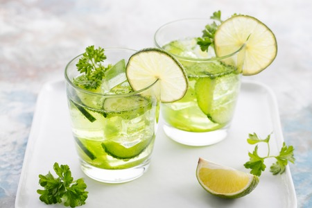 lemon water: Lime, cucumber, parsley cocktail, lemonade, detox water with ice cubes in a glasses on a white plate