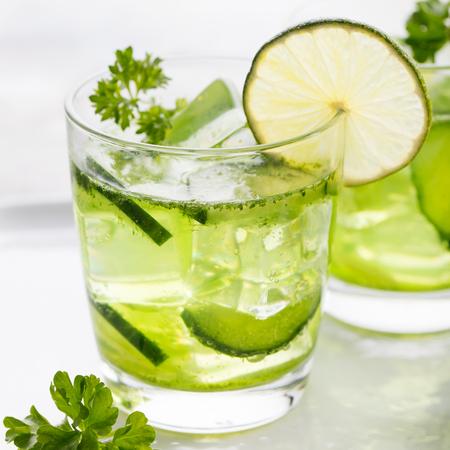 water glass: Lime, cetrioli, cocktail prezzemolo, limonata, acqua disintossicazione con cubetti di ghiaccio nei vetri su un piatto bianco