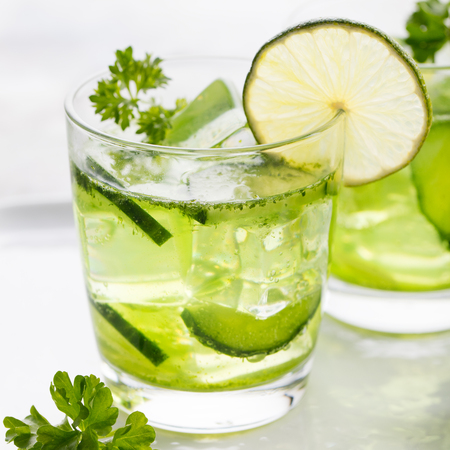 infused: Lime, cucumber, parsley cocktail, lemonade, detox water with ice cubes in a glasses on a white plate