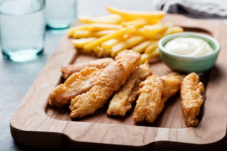 chips: Crispy Fish and Chips with Tartar Sauce Traditional British food on a wooden board Stock Photo
