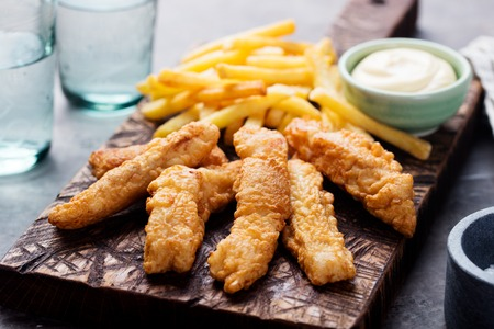 prepared fish: Crispy Fish and Chips with Tartar Sauce Traditional British food on a wooden board Stock Photo