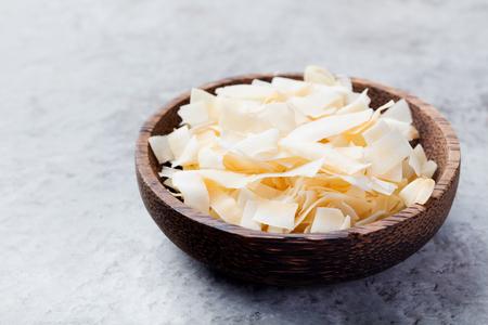 有機ロースト ココナッツ チップ フレーク砂糖と塩木製ボウル石背景