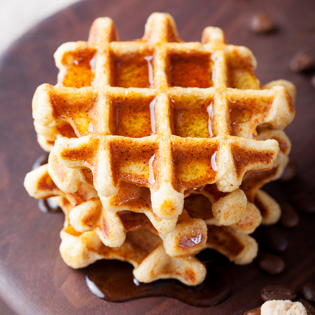 Fresh whole wheat waffles with ice cream, maple syrup and coffee on a wooden background