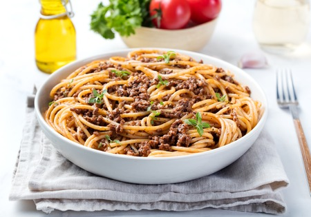 Spaghetti bolognese with cheese and basil on a plate Italian ingredients background