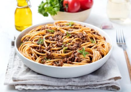 Espagueti boloñés con queso y albahaca sobre un fondo de placa ingredientes italianos Foto de archivo