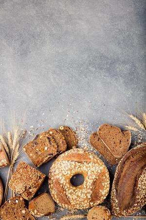 Assortiment van gebakken brood op stenen tafel achtergrond Compositie met sneetjes brood en broodjes kopie ruimte Stockfoto