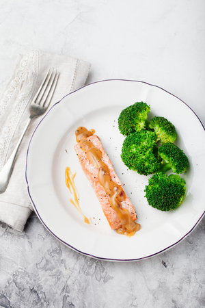 c vitamin: Salmon steak with creamy sauce and broccoli on a white plate