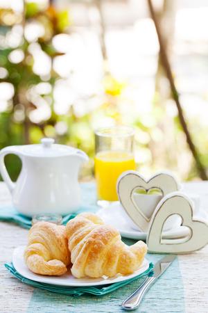desayuno romantico: Desayuno romántico con amor. Cruasanes, café, zumo, corazones de madera. fondo de verano. espacio de la copia Foto de archivo