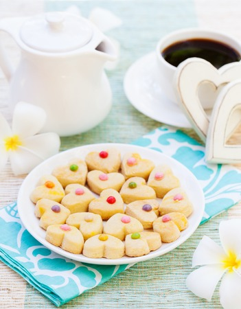 desayuno romantico: Romantic breakfast concept Cup of coffee with sugar icing decorated heart shaped cookies. Cheerful romantic morning