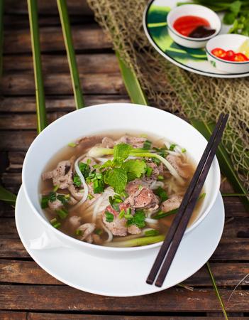 Traditionele Vietnamese pho van de rundvleessoep op een houten achtergrond