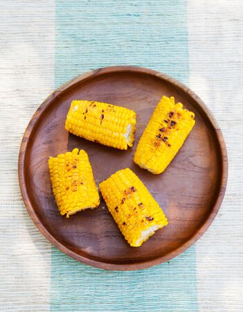 elote: La parrilla de maíz en la mazorca con la sal y la mantequilla en una placa de madera Vista superior del espacio de copia Foto de archivo
